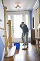 Free Stock Photo: An African-American man mopping his home floor