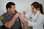 Free Stock Photo: A police officer receiving a vaccination shot from his doctor