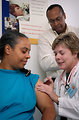 Free Stock Photo: A nurse giving a middle-aged woman a vaccination shot