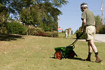 Free Stock Photo: A man fertilizing his lawn with a spreader