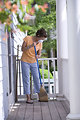 Free Stock Photo: A woman sweeping her front porch