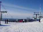 Free Stock Photo: Skiers and chair lifts on the top of a mountain