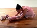 Free Stock Photo: A young ballerina in pink stretching on a wooden floor