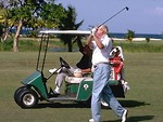 Free Stock Photo: Man swinging a golf club standing next to a golf cart