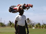 Free Stock Photo: Man carrying a set of golf clubs on his head