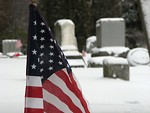 Free Stock Photo: Closeup of a US flag in a snow coverd graveyard