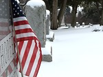 Free Stock Photo: Closeup of a US flag and tombstone in a snow covered graveyard