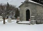 Free Stock Photo: A small mausoleum with US flags in a snow covered graveyard