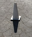 Free Stock Photo: A white construction pylon on black pavement