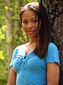 Free Stock Photo: A beautiful African American teen girl posing against a tree in the woods