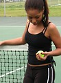 Free Stock Photo: A beautiful African American teen girl on an tennis court with a tennis ball