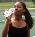 Free Stock Photo: A beautiful teen African American girl drinking water on a tennis court