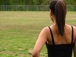 Free Stock Photo: A beautiful teen African American girl looking over an athletic field.