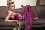 Free Stock Photo: A beautiful woman in a purple dress sitting on a couch