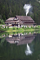 Free Stock Photo: A chalet at the base of a mountain reflecting in water