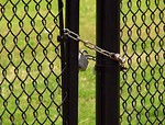 Free Stock Photo: A chain and padlock on a fence by a field