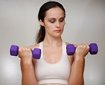 Free Stock Photo: A beautiful young woman exercising with weights