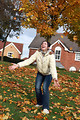 Free Stock Photo: A girl playing in autumn leaves by a house