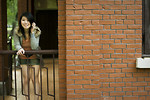 Free Stock Photo: A beautiful Chinese girl posing on a railing by a brick wall