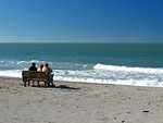 Free Stock Photo: People sitting on a bench overlooking the ocean
