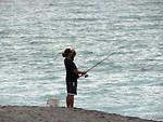 Free Stock Photo: A man fishing on the beach